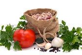 Bonen in een zak omringd door tomatoe, knoflook, peper en peterselie geïsoleerd — Stockfoto