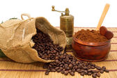 Coffee beans spilled out of the bag, ground coffee in a bowl, spoon, little heart and coffee grinder — Stock Photo
