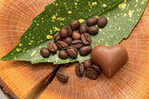 Coffee beans on the leaf with chocolate heart — Stock Photo