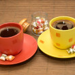 Yellow and orange cup of coffee with colorful candies and glass bowl between them — Stock Photo #45180183