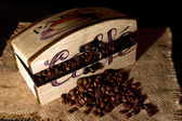 Box filled with coffee beans on jute table cloth on dim light — Zdjęcie stockowe