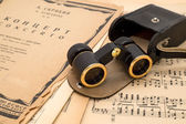Opera glasses with case on an ancient music score — Foto Stock