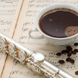 Silver flute, cup of coffee and coffee beans on an ancient music score — Stock Photo #45210937
