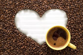 White paper in heart shape with yellow cup of coffee — Stock Photo