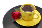Cup of coffee with beautiful red rose on black record — Stock Photo