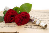 Flute and beautiful red rose on an ancient music score — Stock Photo