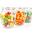 Glass jars filled with different colorful candies isolated on white — Stock Photo #48361209