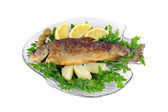 Roasted trout on the fish plate with parsley, lemon, potato and olives isolated on white — Stock Photo
