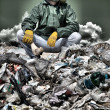 Man in a gas mask sitting on the garbage and holding a bone — Stock Photo #48373867