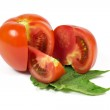 Sliced fresh red tomatoes on green leaves isolated on white — Stock Photo #48662567