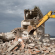 Bulldozer removes the debris from demolition of old derelict buildings — Stock Photo #48875563