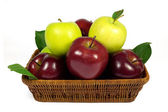Fresh red and green apples with leaves in wicker basket isolated on white — Stock Photo