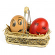 One Brown and One Red Egg with Funny Face in a Wicker Basket Isolated on White — Stock Photo #50859943