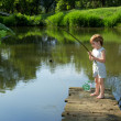 Cute Little Boy Fishing from the Edge of Wooden Dock and Patiently Waiting for his Catch in Sunny Day — Stock Photo #50974343