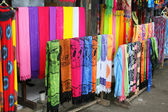 Rows of colourful silk scarfs hanging at a market stall in Indon — Stock Photo