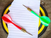 Darts arrows on white paper — Stock Photo
