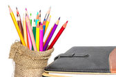 Colour pencils and notebook on white background — Stock Photo