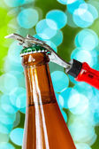 Opening dark beer bottle with metal opener — Stock Photo