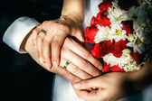 Bride and groom's hands with wedding rings, wedding bouquet. — Stock Photo
