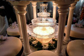 Table decoration of champagne fountain in light and wedding cake — Stock Photo