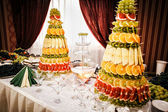 Champagne fountain and decorations from fruit on table setting a — Stock Photo