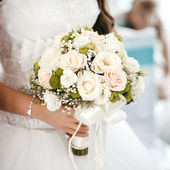 Bride holding wedding bouquet from roses at a wedding ceremony — Stock Photo