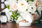 Gold wedding rings in white gift box in shape of heart and wedding bouquet. — Stock Photo