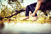 Young couple in love sitting cross-legged on a tree branch above river — Stock Photo