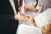 Wedding ceremony in church. Priest puts a wedding ring on groom's finger — Stock Photo