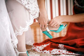 Bridesmaid helps to bride to put on cyan wedding shoes. — Stock Photo