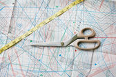 Background with pattern, measuring tape and scissors. Focused on — Stock Photo