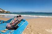 Tasche, handtuch und sonnenbrille am strand — Stockfoto
