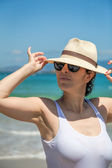 Pretty woman in hat and sun glasses on the beach — Stock Photo