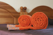 Rolled orange towels on the violet covered bed — Stock Photo