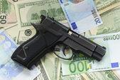 Money as a backdrop and a gun — Stock Photo