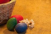 Easter Eggs and a Basket on sackcloth background — Stock Photo