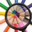 Magnifier and colored pencils — Stock Photo