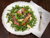 Rucola salad with grilled bacon and parmesan — Stock Photo
