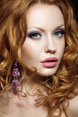 Beautiful red-haired girl with bright makeup and curls. — Stock Photo