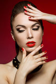 Beautiful woman with evening make-up and red nails with thorns. — Stock Photo
