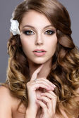 Beautiful girl in wedding image with flowers in her hair — Stock Photo