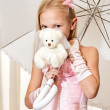 Little girl holding umbrella and wedding teddy-bear — Stock Photo