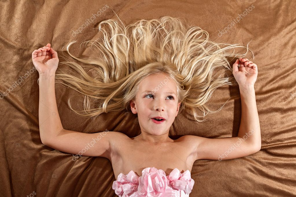 Surprised little girl lying on bed — Stock Photo