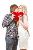 Happy couple kissing and holding red valentine's heart  — Stock Photo