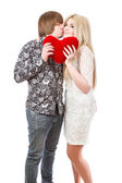 Happy couple kissing and holding red valentine's heart  — Stockfoto