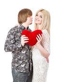 Casal feliz beijos e segurando o coração vermelho do dia dos namorados — Fotografia Stock
