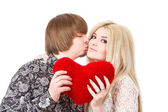 Happy couple kissing and holding red valentine's heart  — ストック写真