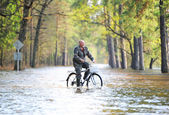The man by bicycle goes on the flooded road — Stock fotografie