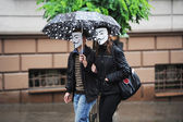 People in masks under umbrellas — Foto Stock