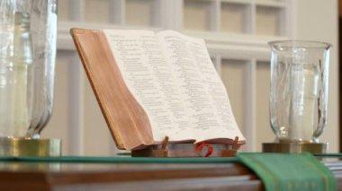 Una biblia abierta se encuentra entre dos velas en un altar — Vídeo de Stock